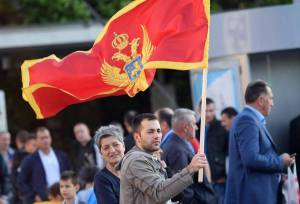 epa05321914 A man holds the Montenegrin flag at the Independence Square during the celebrations for the country's 10th anniversary of its Independence Day in Podgorica, Montenegro, 21 May 2016. EPA/BORIS PEJOVIC